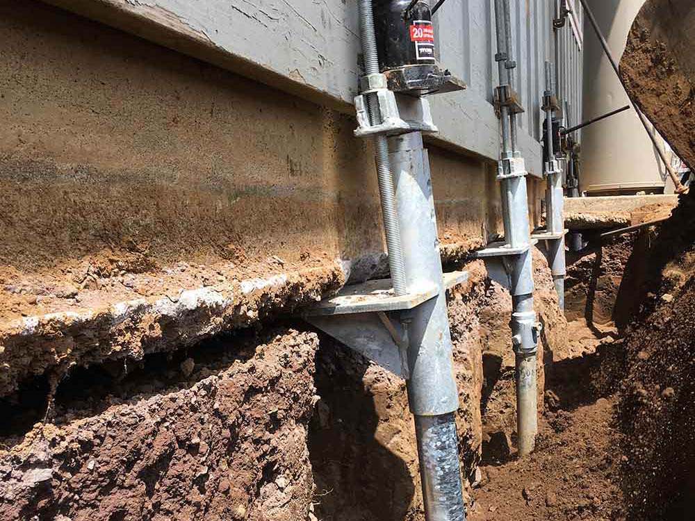 Foundation being raised using micropiles